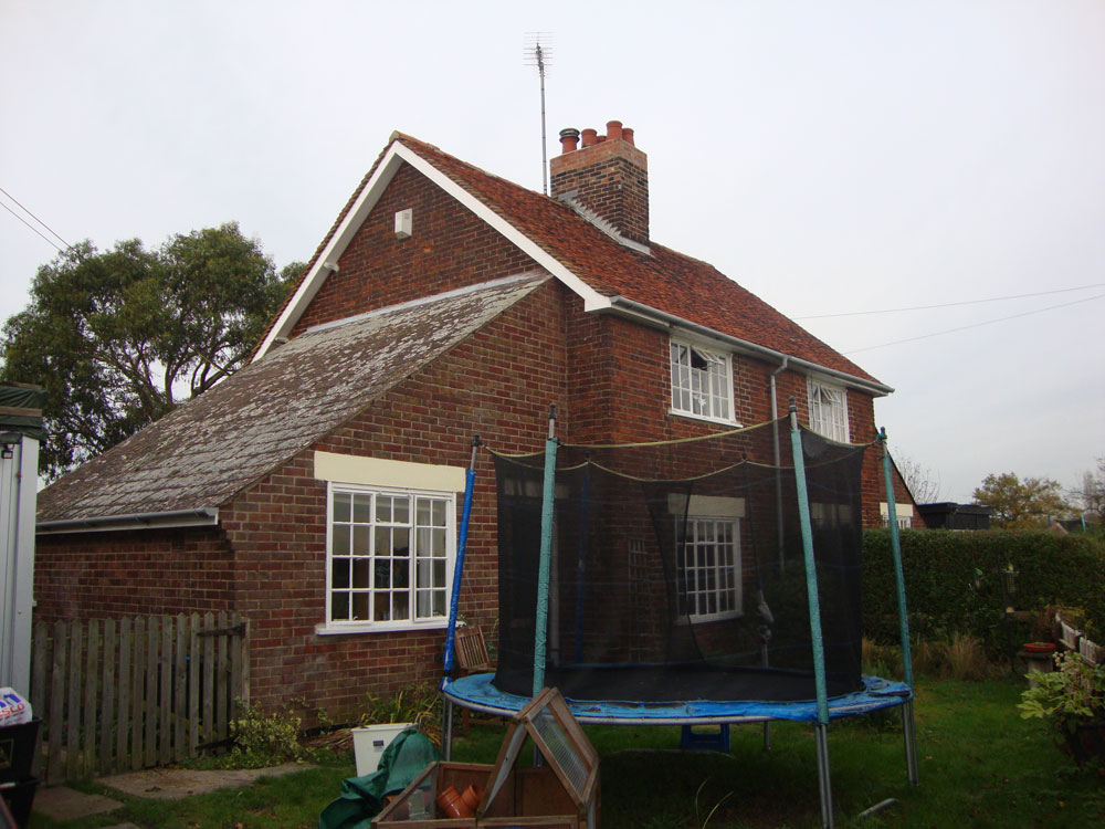 Before photo showing front and side of cottage