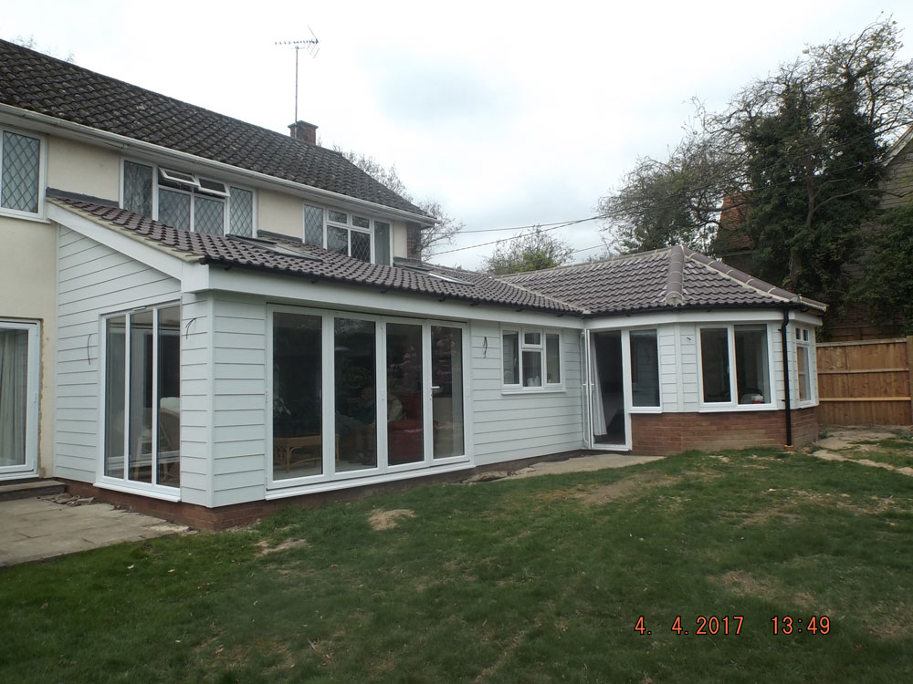 Rear single storey extension finished with weatherboarding and pan tiled roof.