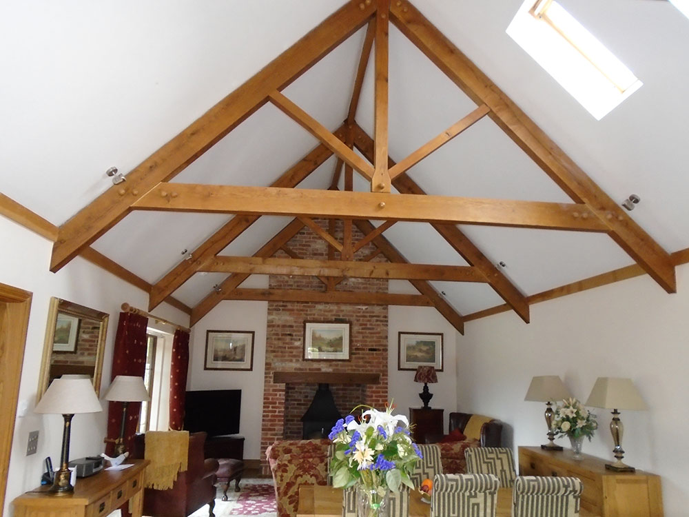 Open plan living accommodation with vaulted ceiling, exposed roof trusses and open fire with log burner