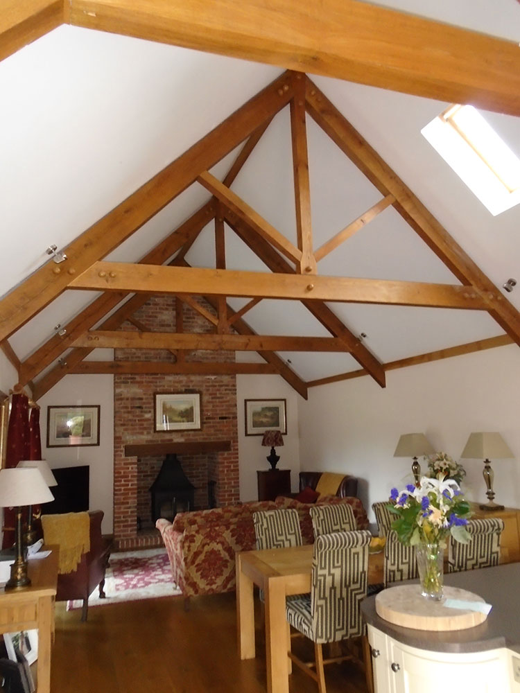 Annexe open plan living accommodation with vaulted ceiling, exposed roof trusses and open fire with log burner