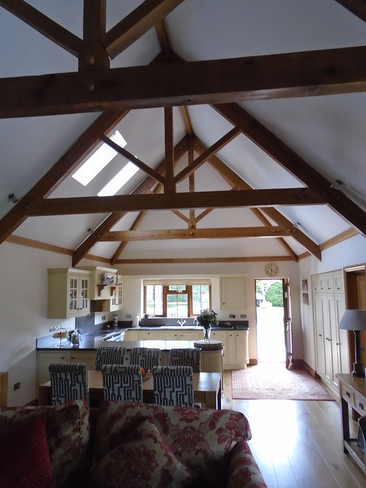 Annexe living accommodation showing open plan kitchen and dining area with vaulted ceiling and exposed roof trusses